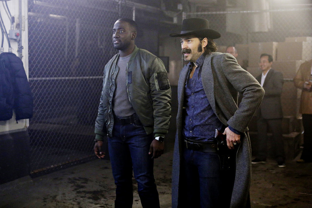 """WYNONNA EARP -- """"Two-Faced Jack"""" Episode 108 -- Pictured: (l-r) Shamier Anderson as Agent Dolls, Tim Rozon as Doc Holliday -- (Photo by: Michelle Faye/Syfy/Wynonna Earp Productions)"""