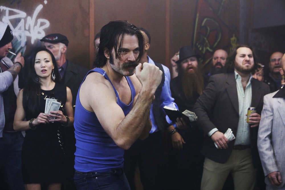"WYNONNA EARP -- ""Two-Faced Jack"" Episode 108 -- Pictured: Tim Rozon as Doc Holliday -- (Photo by: Michelle Faye/Syfy/Wynonna Earp Productions)"