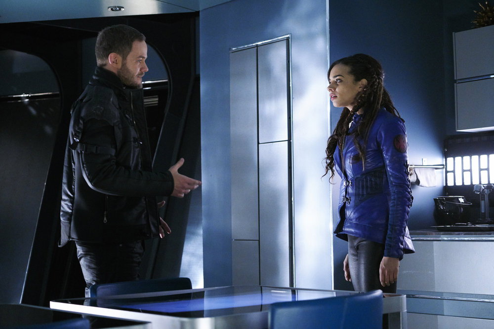 """KILLJOYS -- """"Dutch and the Real Girl"""" Episode 201 -- Pictured: (l-r) Aaron Ashmore as John, Hannah John-Kamen as Dutch -- (Photo by: Steve Wilkie/Syfy/Killjoys II Productions Limited)"""